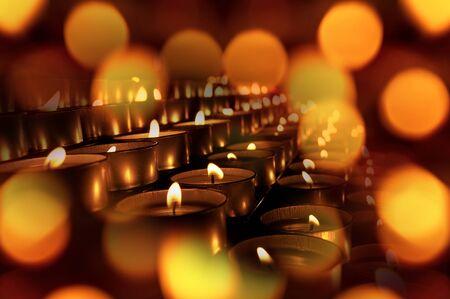 Gros plan sur un groupe de bougies votives, bougies chauffe-plat, avec effet bokeh. Fond chaud