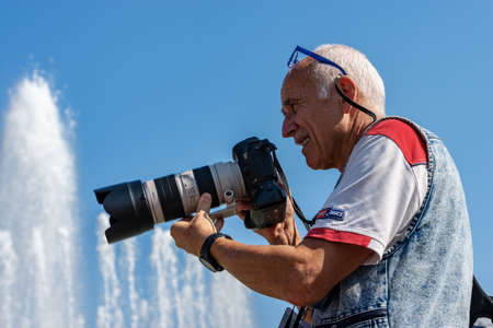 Male photographer with professional equipment (Canon EOS Mark III) while he is performing a photo shoot in downtown of Milan in front of the Sforza Castle