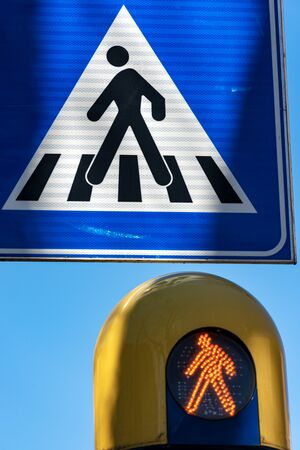 Close-up of a crosswalk sign and an orange pedestrian traffic light. Trento, Trentino-Alto Adige, Italy, Europe