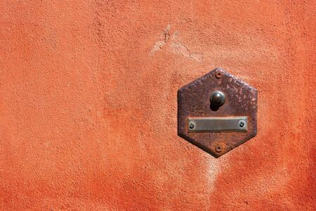 Close-up of an old doorbell with empty nameplate on a red wall with copy space. Tellaro village, Liguria, Italy, Europe