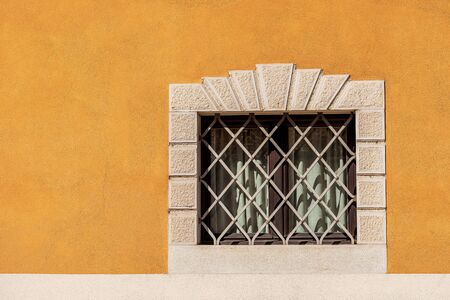 Small window with wrought iron security bars on an orange and white wall. Trentino Alto Adige, Italy, Europe