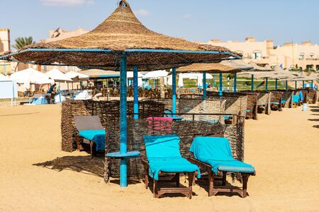 Group of straw umbrellas and deck chairs in a Red Sea sandy beach, tourist resort near Marsa Alam, Egypt, Africa