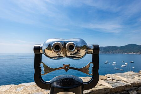 Coin operated electronic binoculars for tourists on a blurred seascape with boats. Vernazza village, Cinque Terre, National park in Liguria, La Spezia, Italy, Europe.