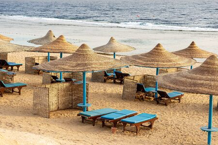 Red Sea beach with straw umbrellas and deck chairs near Marsa Alam, Egypt, Africa. The waves of the sea crash on the coral reef 写真素材