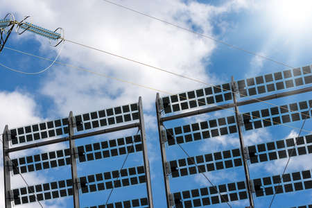 Solar panels and a power line on a blue sky with clouds and sun rays. Renewable Energy concept Zdjęcie Seryjne