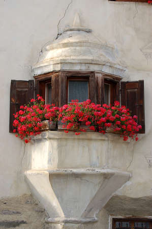Old balcony with wooden windows and red geraniums in the ancient village of Guarda, Scuol municipality, Engadin valley, Graubunden canton, Switzerland, Europe