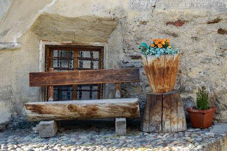 Empty wooden bench and flower pot made of tree trunks, Engadin valley, Graubunden canton, Switzerland, Europe Stok Fotoğraf