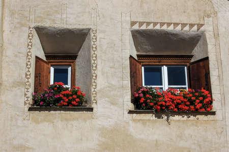 Two old wooden windows with decorations and red geraniums in the ancient village of Samedan, tourist resort in Engadin valley, Graubunden canton, Maloja region, Switzerland, Europe
