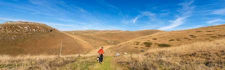 LESSINIA PLATEAU, VENETO, ITALY, NOV 1th, 2016: a group of hikers with a dog walk on a grassy path on the Lessinia plateau, Italian Alps, Regional Natural Park, Verona province, Veneto, Italy, Europe