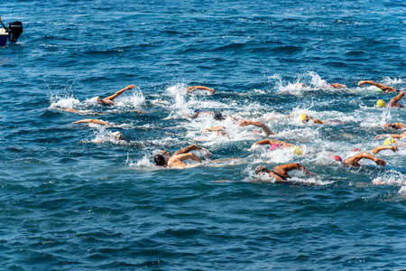 TELLARO, GULF OF LA SPEZIA, LIGURIA, ITALY - JULY 21th, 2019: Swimming competition in the Mediterranean sea (Trofeo del Gro), in front of the ancient village of Tellaro. A group of freestyle swimmers is competing in the blue water
