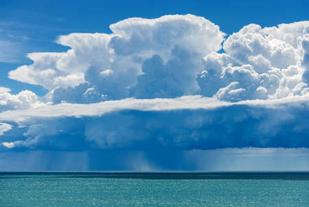 White clouds in the Blue Sky. Cumulonimbus with torrential rain over the Mediterranean sea. Gulf of La Spezia, Liguria, Italy, Europe