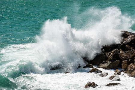 Large white waves of the Sea Break on the Rocks. Breakwater in the Gulf of La Spezia, Liguria, Italy