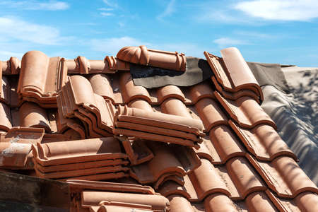 Closeup of a roof under repair with terracotta orange tiles (Coppo in Italian language). Blue sky with clouds on background. Italy, Europe Banque d'images