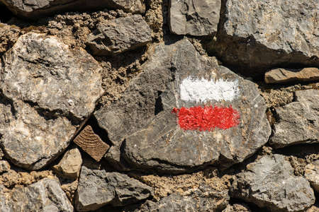 Closeup of a red and white Trail Sign on a stone wall, footpath in Liguria, Italy, Europe