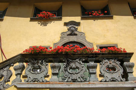 Ancient house with stone balcony, door and windows with red geraniums, ancient village of Zuoz, tourist resort in Engadin valley, Graubunden canton, Maloja region, Switzerland, Europe