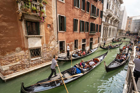Venice, Many gondoliers and tourists on the gondolas, typical Venetian rowing boat. Sightseeing tour along the Canals of the famous city. Veneto, Italy, Europe.