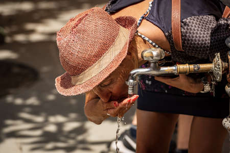 An adult woman with straw hat, drinking water on a hot summer day in Vernazza village, Cinque Terre, Liguria, Italy, Europe.