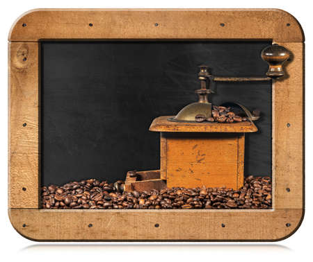Old manual coffee grinder made of metal and wood with roasted coffee beans in a blackboard with copy space, isolated on white background.