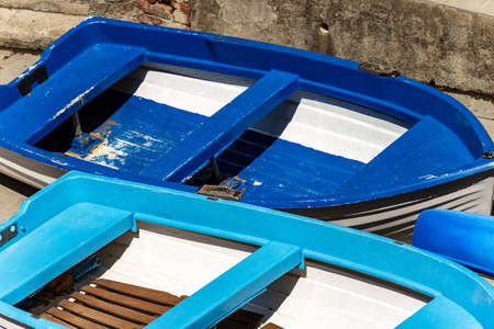 Close-up of blue and white small boats moored on the quay of the harbor in Liguria, Italy, Southern Europe.