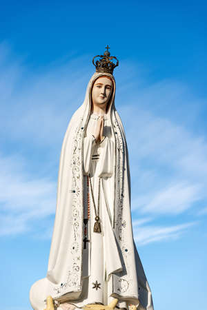 Closeup of a statue of Statue of Virgin Mary, mother of Jesus Christ, with crown and rosary on blue sky with clouds. Archivio Fotografico