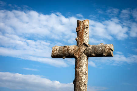 Ancient christian cross made of stone on blue sky with clouds (imitation of a tree trunk), near the small village of Sant'Anna d'Alfaedo, Lessinia plateau, Verona, Italy, Europe.