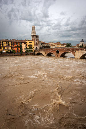 Verona, Ponte Pietra (Stone bridge), I century B.C, and Adige river in flood after several violent storms. UNESCO world heritage site, Veneto, Italy, Europe