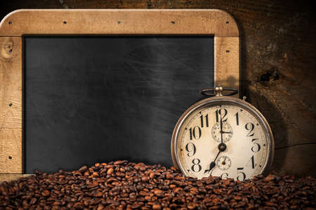 Closeup of an old alarm clock and a pile of roasted coffee beans on an empty blackboard with wooden frame and copy space.