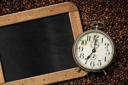 Closeup of an old alarm clock on background with many roasted coffee beans and empty blackboard with wooden frame and copy space.