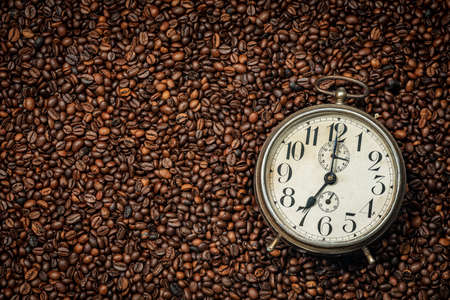 Closeup of an old alarm clock on background with many roasted coffee beans and copy space, full frame.