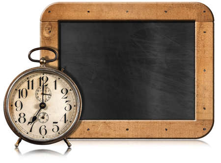 Old alarm clock, seven o'clock, and empty blackboard with wooden frame and copy space, isolated on white background.