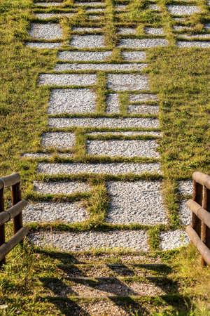 Outdoors paving made of limestone slabs on green lawn, stones called Lessinia or Prun. Lessinia plateau, Verona province, Veneto, Italy, Europe.