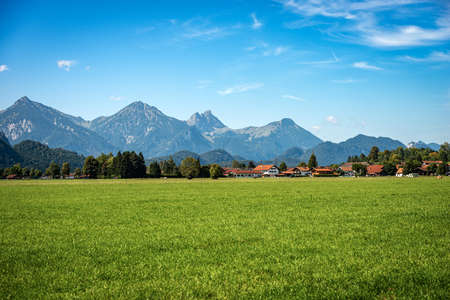Green Agricultural Fields and Bavarian Alps with the small town of Schwangau near Fussen, Ostallgau, Bavaria, Germany. Archivio Fotografico