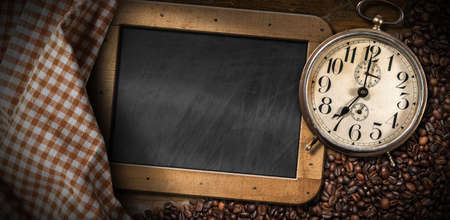 Old alarm clock, seven o'clock, on a wooden table with roasted coffee beans, empty blackboard and checkered tablecloth. Archivio Fotografico