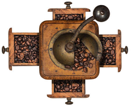 Old manual coffee grinder made of metal and wood with roasted coffee beans and four drawers, isolated on white background. Top view. Italy.