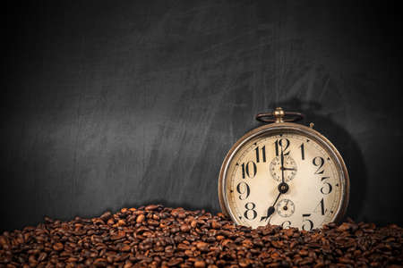 Closeup of an old alarm clock and a pile of roasted coffee beans on an empty blackboard with copy space.