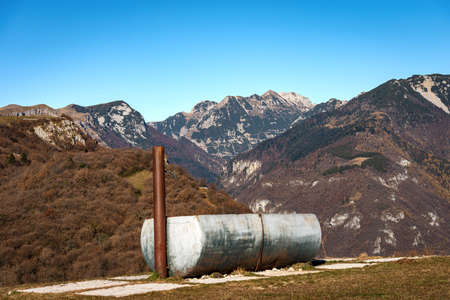 Mountain Range of the Monte Carega, called the small Dolomites, view from the Lessinia Plateau (Altopiano della Lessinia), and a metal water trough for cows. Verona province, Veneto, Italy, Europe. 免版税图像