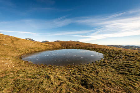 Small lake for cows on Lessinia Plateau, Regional Natural Park, in the background the Monte Carega called the small Dolomites. Verona Province, Veneto, Italy, Europe. 免版税图像