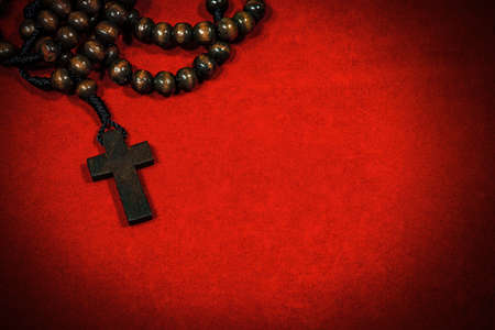 Closeup of an old wooden crucifix with rosary beads on a red velvet background with copy space.