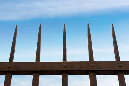 Close-up of a wrought iron fence with sharp points on blue sky with clouds and copy space