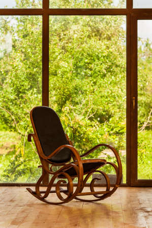 easy chair: Vintage rocking chair near a large window