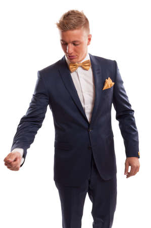 Male model wearing an elegant blue suit with a golden bowtie and handkerchief photo