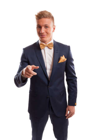 Elegant man wearing a blue suit with golden bow tie and handkerchief pointing at something photo