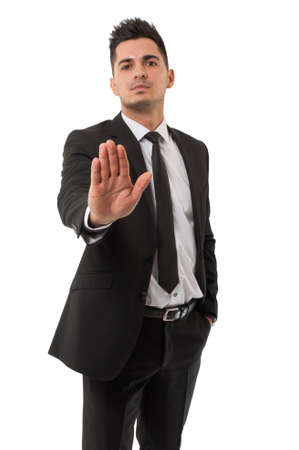 Business man wearing a classic black suit is  saying stay right there by using his right hand