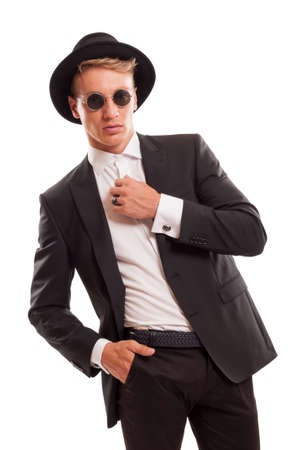 Classy and elegant male model posing wearing designer clothes with a fancy hat and some round sun glasses, 60s model photo