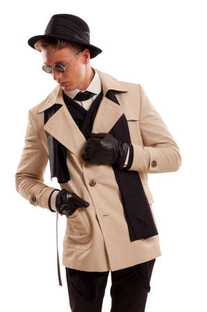 Elegant detective posing wearing a coat, sun glasses and a fancy hat on a white background in a photo studio photo