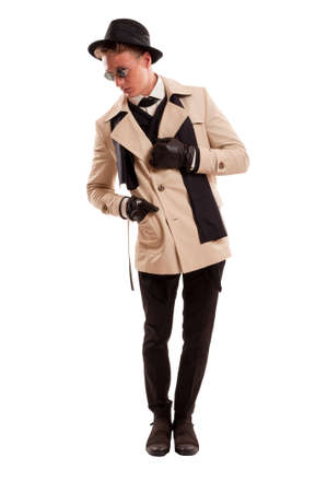 Elegant male model posing dressed with a detective coat, fancy hat and round sun glasses in a photo studio isolated on a white background photo