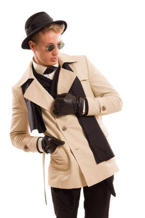 Handsome detective with a good sense on fashion posing in a photo studio wearing a coat, fancy hat and sun glasses, all isolated on a white background photo
