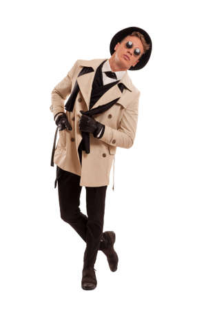 Male model wearing a detective coat posing in a photo studio with attitude, isolated on a white background photo