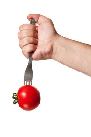A white male hand stucking an iron fork in a beautiful red tomato on a white background photo