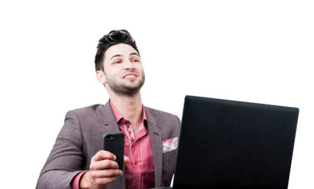 Happy business man laughing and holding a smartphone, and having a laptop on his desk. Everything on a white background. photo